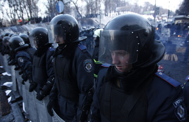 Riot police stand at their position near the site of clashes with anti-government protesters in Kiev