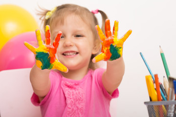 A girl shows palms in paint