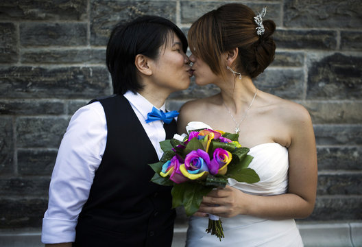 """A couple kiss as they pose for a picture before taking part in """"The Celebration of Love"""", a grand wedding where over 100 LGBT couples will get married, at Casa Loma in Toronto"""