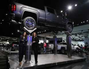 GMC's Parks and Emsley pose underneath a GMC Denali HD pickup truck at the North American International Auto Show in Detroit