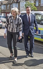 Britain's Prime Minister David Cameron and Home Secretary Theresa May accompany immigration enforcement officers into a home in Southall following an early morning raid in west London, Britain