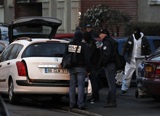 French crime scene investigating police place bags of evidence inside a car seen outside the five-storey apartment building where earlier special forces police staged the assault on the gunman Mohamed Merah in Toulouse
