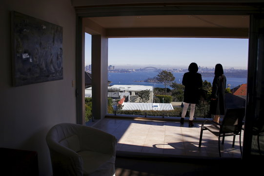 The Sydney Opera House and Harbour Bridge can be seen behind real estate agent LuLu Sun (R) as she escorts Bao Fang, a potential buyer from Shanghai, during an inspection of a property for sale in the Sydney suburb of Vaucluse, Australia
