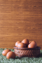 Eggs in wooden basket on green grass. Free space for text