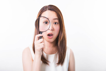 Surprised young woman looking through a magnifying glass on a white background