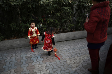 A boy, dressed in traditional Chinese clothes, reacts as his grandmother tries to take a picture of him and his sister with a mobile phone, on a busy street in downtown Shanghai