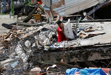 A man retrieves goods from a collapsed shop following a strong earthquake in Meureudu, Pidie Jaya, Aceh province