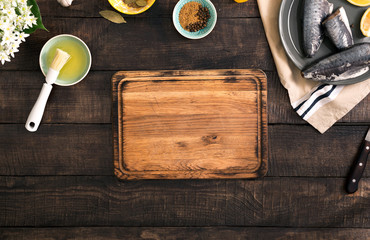 Empty kitchen board on wooden table with fresh raw fish