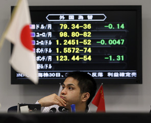 A foreign exchange broker sits in front of a monitor displaying major currency rates against the Japanese yen and the U.S. dollar at a trading room in Tokyo
