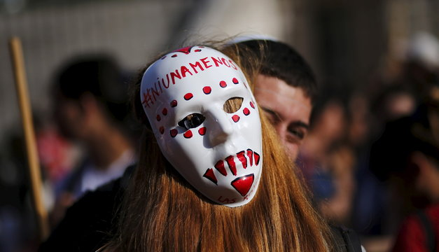 A woman wears a mask as she kisses a man during a demonstration to mark International Women's Day and to demand policies to prevent femicides outside the Congress in Buenos Aires