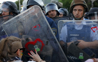 A demonstrator draws a heart shape on a police shield during a protest against the government, in front of the EU office in Skopje