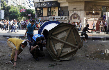 Protesters hide behind a bank security booth as they throw stones at police near the U.S. embassy in Cairo