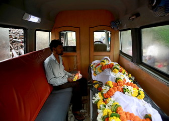 Relative sits inside an ambulance with the body of a victim who died after consuming bootleg liquor at a cremation ground in Mumbai