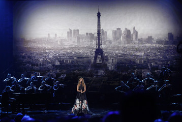 "Celine Dion performs ""Hymne a l'amour"" in honor of the victims of the recent Paris attacks as an image of the Eiffel Tower is shown in the background during the 2015 American Music Awards in Los Angeles"