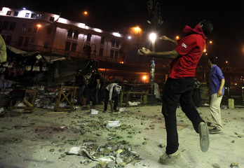 Supporters of deposed Egyptian President Mohamed Mursi throw stones towards riot police during clashes on the Sixth of October Bridge over the Ramsis square area in central Cairo