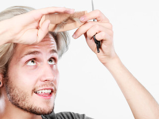 Man with scissors and comb creating new coiffure