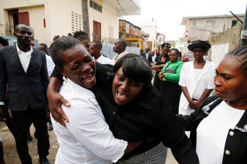 Relatives react during the funeral of a woman who died during Hurricane Matthew in Jeremie