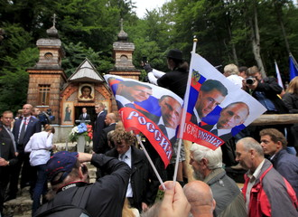 People wave flags depicting images of Russian Prime Minister Dmitry Medvedev and President Vladimir Putin during the commemoration of the Russian Chapel in Vrsic