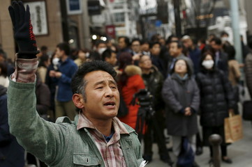 A man sings a Japanese song after bells tolled to mark the moment the March 11, 2011 earthquake struck Japan, at a junction in Tokyo