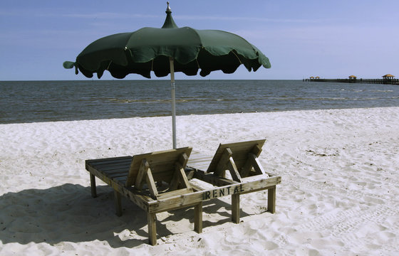 A vacant rental beach chair and umbrellla are seen on the beach in Gulfport