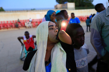 A disabled woman takes photos with a mobile phone as she attends the first wheelchair basketball tournament in Sudan, marking the International Day of Persons with Disabilities, at the Omdurman Youth Centre, Sudan