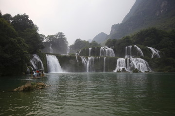 Tourists stand on a improvised boat to take photos in front of Ban Gioc waterfall, which borders China, in Cao Bang province, Vietnam
