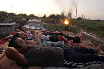 Migrants workers from Tajikistan relax on the roof of their shelter after working at local market outside Moscow