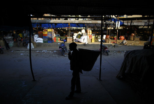Porter is silhouetted as he smokes a cigarette inside a vegetable market in Kathmandu