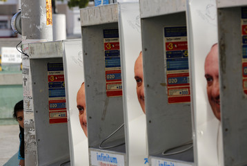 A girl peeks from behind public telephone booths with photographs of Pope Francis in Tuxtla Gutierrez