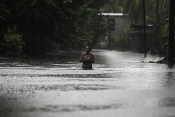 A woman wades through a flooded street in Puerto San Jose in the Escuiltla region