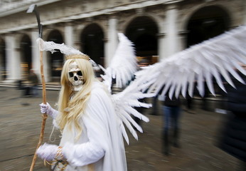 A masked reveller poses in San Marco Piazza during the Venice Carnival