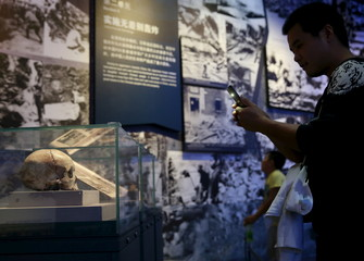 A visitor takes a picture of the skull of a victim of the Nanking Massacre at the Museum of the War of Chinese People's Resistance Against Japanese Aggression, in Beijing