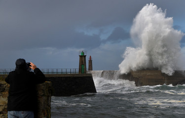 A man takes a picture of the waves as they crash against a lighthouse in the northern Spanish village of Viavelez