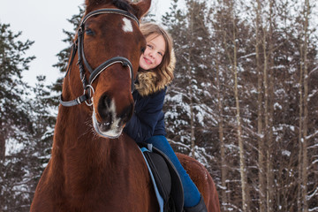 Girl teenager and big horse in a winter
