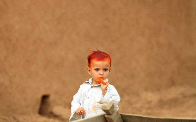 Three-year-old boy Zubair, with henna-dyed hair, eats a popsicle while standing outside his mud house in the outskirts of Islamabad