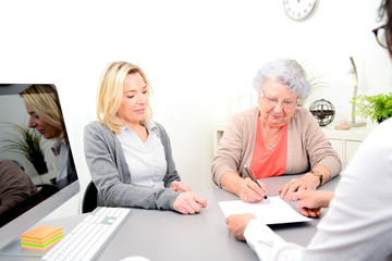 elderly senior woman with daughter signature legacy heritage testament document in a lawyer notary office Fototapete