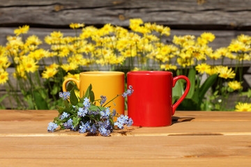 Warm drinks for the spring-summer mood/ Mugs standing together on a table next to a bouquet of blue flowers on the street near the house