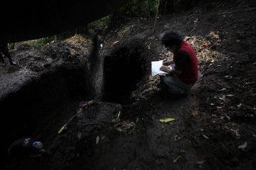 An anthropologist take notes outside a mass grave in the former Regional Command headquarters of the Guatemalan Army in Coban