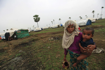 A woman from the Pauktaw township carries her son in a Rohingya internally displaced persons camp outside Sittwe