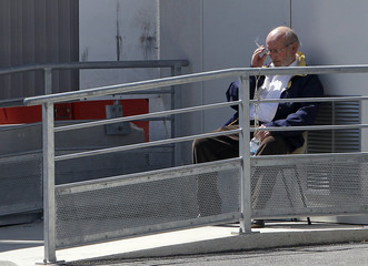 PIP founder Mas smokes a cigarette during a break at the courthouse for the trial of PIP breast implant company in Marseille