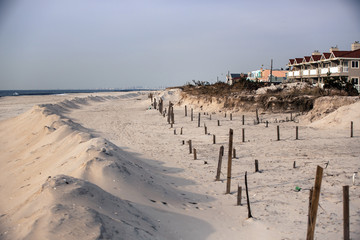 Man-made sand piles stand in front of wooden beams used in an attempt to stabilize dunes that have been erased by the storm surge of superstorm Sandy in Long Beach, New York