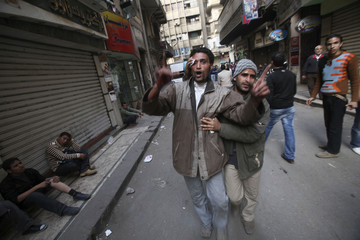 Injured demonstraters help each other during rioting between pro and anti-Mubarak supporters in Tahrir Square in Cairo