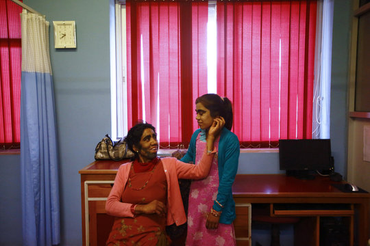 Budhathoki looks at her daughter Manjura's face after it was shaved during laser hair removal treatment at Dhulikhel Hospital in Kavre