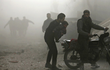 A man carries an injured child to a motorcycle at a site hit by what activists said was an air strike by forces of Syria's President al-Assad in the Duma neighbourhood of Damascus
