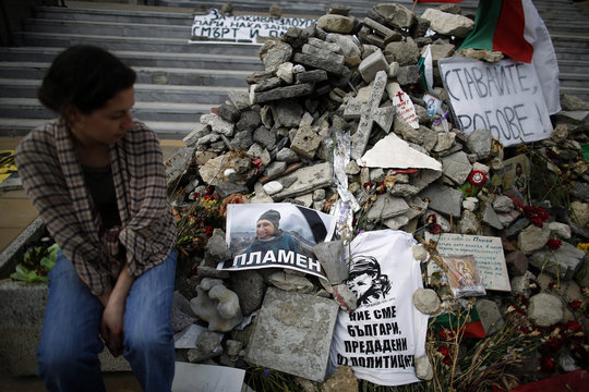 Petrova sits next to a pile of stones left by friends and fellow protesters at the spot where artist Goranov set himself on fire in the city of Varna