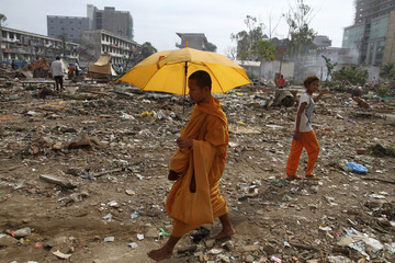 A Buddhist monk walks past houses that were destroyed, a day after residents were evicted in Phnom Penh