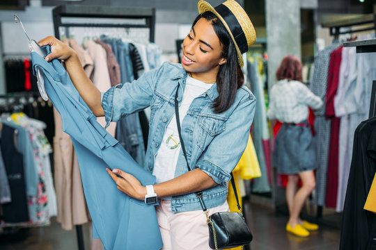 african american hipster girl choosing clothes in shopping mall, boutique shopping concept