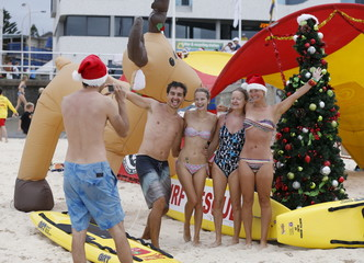Visitors to Sydney's Bondi Beach pose for a picture in front of a decorated Christmas tree and an inflatable reindeer on Christmas Day