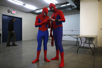 "Applicants dressed up as Spider-Man look through pictures on a phone as they wait for their turn to audition to be a part of a promotional campaign for the upcoming release of ""The Amazing Spider-Man 2"" in Chicago"
