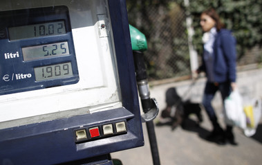 A woman walks past a meter at a petrol station in downtown Rome